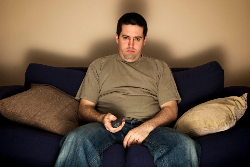 скучный одинокий мужик у скучного телевизора